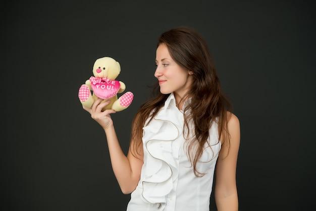 Haar genegenheid en liefde tonen. sensueel meisje houdt teddybeer vast. leuk liefdescadeau. cadeau uit het hart. ik hou van je inscriptie. valentijnsdag. liefde zit in haar hart.