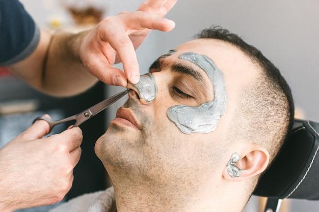 Haar knippen in de neus van een man. mannelijk gezicht waxen. kapper verwijdert haar door zich uit het gezicht van de turkse man te trekken.