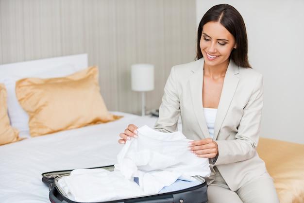 Haar koffer uitpakken. mooie jonge zakenvrouw in pak die haar koffer uitpakt en glimlacht terwijl ze op het bed in de hotelkamer zit