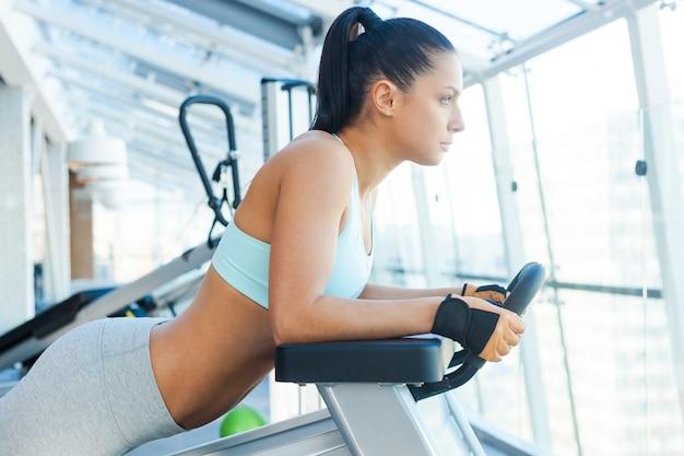 Haar lichaam tot in de perfectie trainen. aantrekkelijke jonge vrouw die geconcentreerd kijkt tijdens het sporten in de sportschool