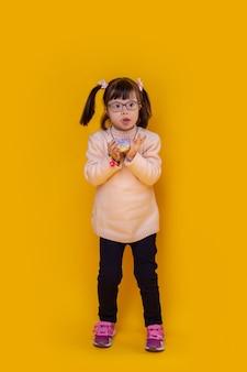 Haar mond openen. aantrekkelijk klein kind met een psychische stoornis die tegen de gele muur blijft en een blauwe donut vasthoudt