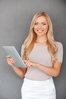 Haar nieuwe gadget testen. glimlachende jonge vrouw die aan digitale tablet werkt en