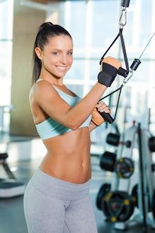Haar perfecte lichaam fit houden. mooie jonge vrouw die in de sportschool traint en glimlacht