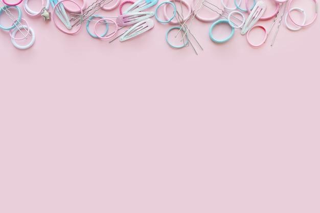 Haar scrunchies en haarspelden op roze achtergrond, schoonheid concept, plat lag