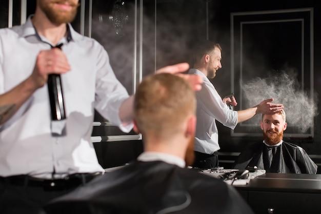 Haar sproeien. portret van een kapper die water op het haar van de cliënt sproeit