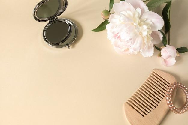 Haarborstel of kam haarspiralen kleine spiegel en grote pioenrozen op een beige achtergrond
