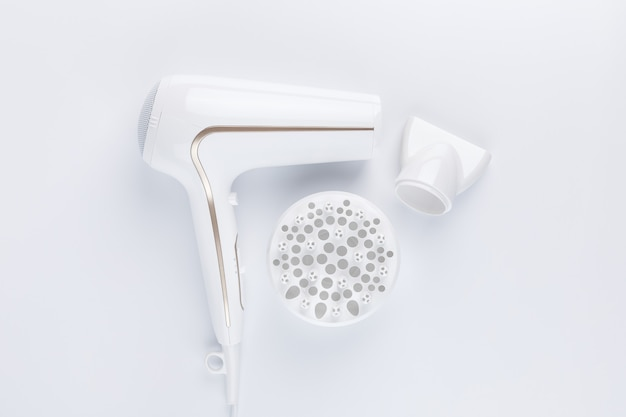Haardroger voor het drogen van haar met een diffuus en plat mondstuk voor styling op een witte achtergrond