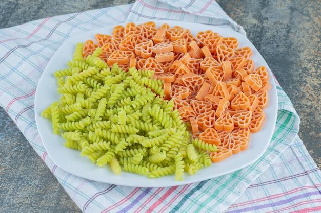 Haardvormige pasta met fusilli pasta in plaat, op de handdoek, op de marmeren achtergrond.