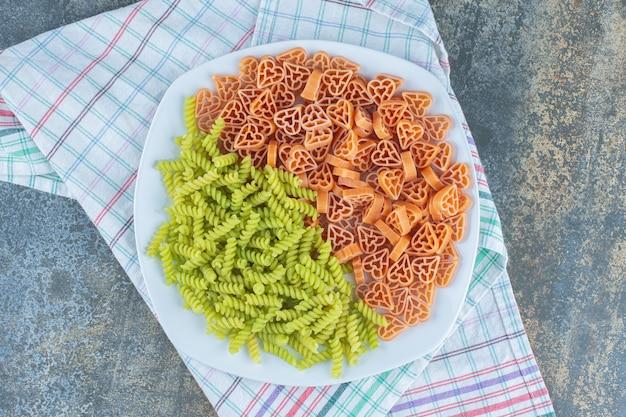 Haardvormige pasta met fusilli pasta in plaat, op de handdoek, op het marmeren oppervlak.