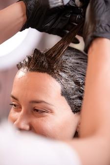 Haarkleuring in de salon, haarstyling. professionele tovenaar schildert het haar in de salon. schoonheid concept, haarverzorging.