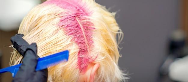Haarkleuring in roze kleur op de haarwortels van jonge blonde vrouw in de kapsalon. selectieve aandacht