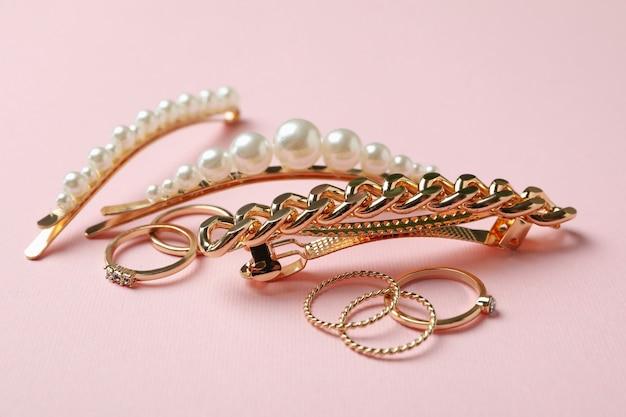 Haarspeldjes en ringen op roze achtergrond