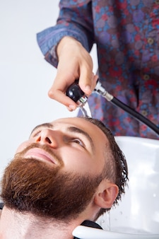 Haarstylen. bijgesneden afbeelding van kapper die het hoofd van zijn cliënt in de kapperszaak wast terwijl hij zich voorbereidt op het knippen