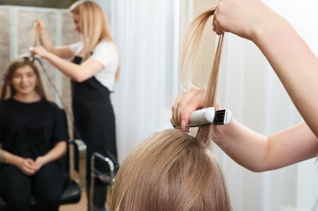 Haarstylist bezig met vrouw client met crimper in salon
