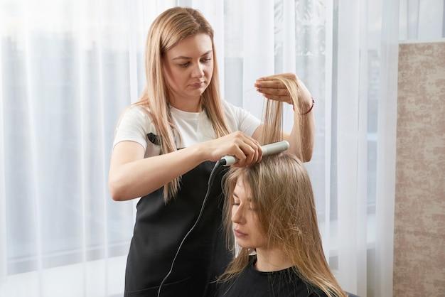 Haarstylist bezig met vrouw client met crimper