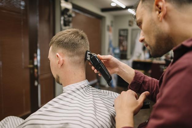 Haarstylist die een kapsel geeft aan een klant