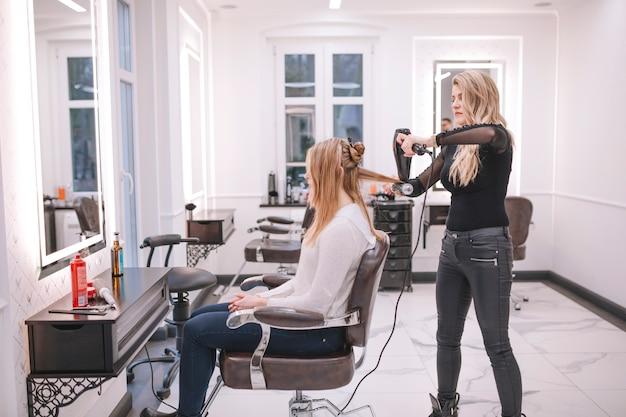 Haarstylist die meisje in salon behandelt