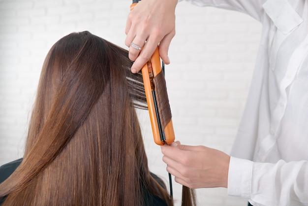Haarstylist die met het bruine haar van de cliënt werkt.