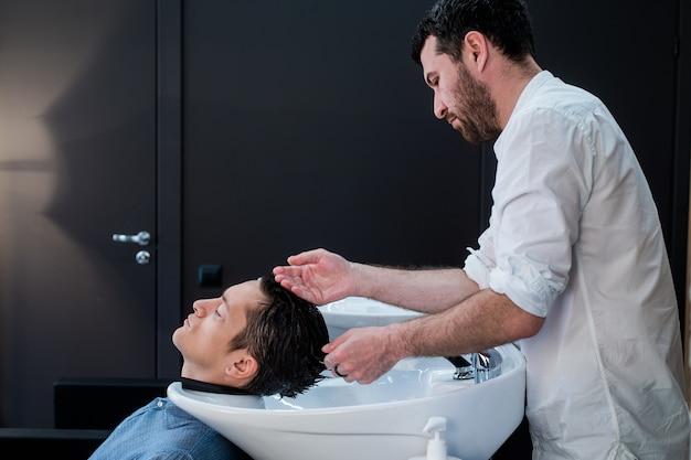 Haarstylist kapper klanten haar wassen