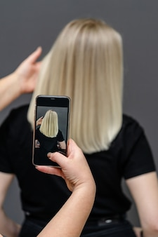 Haarstylist maakt een foto van blonde modellen na het verven en ontkrullen van het haar. reparatie concept