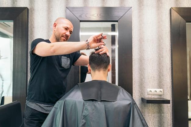 Haarstylist mannen kapsel maken tot een aantrekkelijke man in de schoonheidssalon