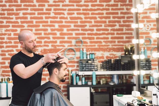 Haarstylist mannen kapsel maken tot een aantrekkelijke man in de schoonheidssalon.