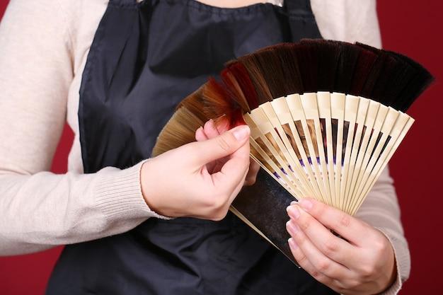 Haarstylist met haarmonsters van verschillende kleuren, close-up, op kleur achtergrond