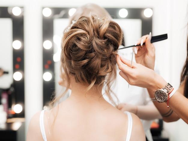 Haarstylist van het meisje maakt een bundel in een schoonheidssalon