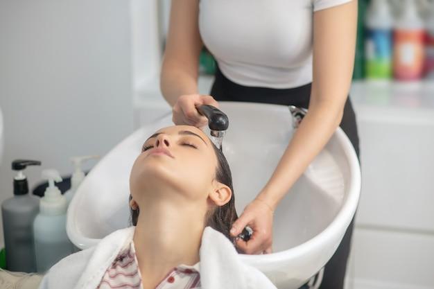 Haarstylist wassen van haar aan haar klant in een kapsalon