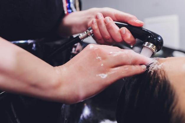 Haarstylist wassen vrouw haar met shampoo.