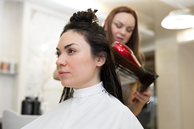Haarstylist werk aan vrouw kapsel in salon. lang bruin haar drogen met een föhn en een ronde borstel