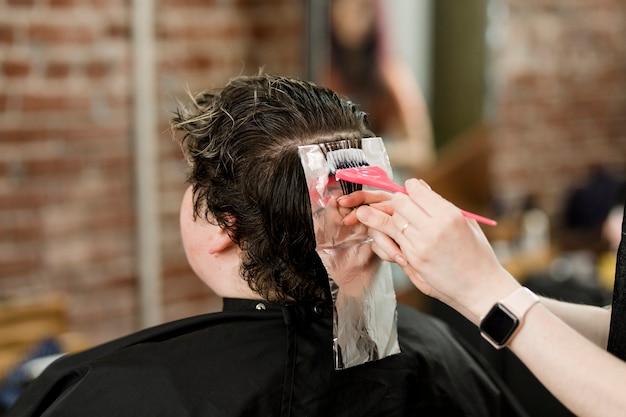 Haarstylist zet het haar van de klant in een permanent