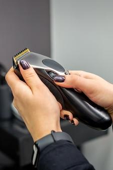 Haartrimmer in handen van vrouwelijke professionele kapper of kapper in de kapsalon