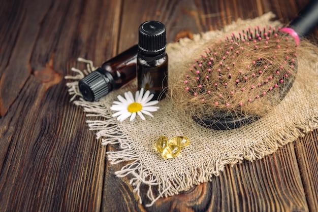 Haaruitval. kammen met haar en etherische oliën, kamille en vitaminecapsules op donker hout.