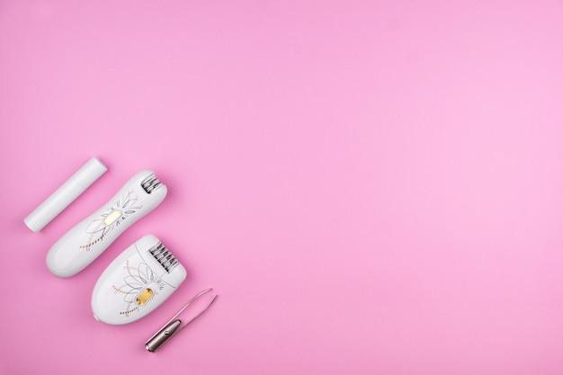 Haarverwijderingsset van vier apparaten op een roze achtergrond