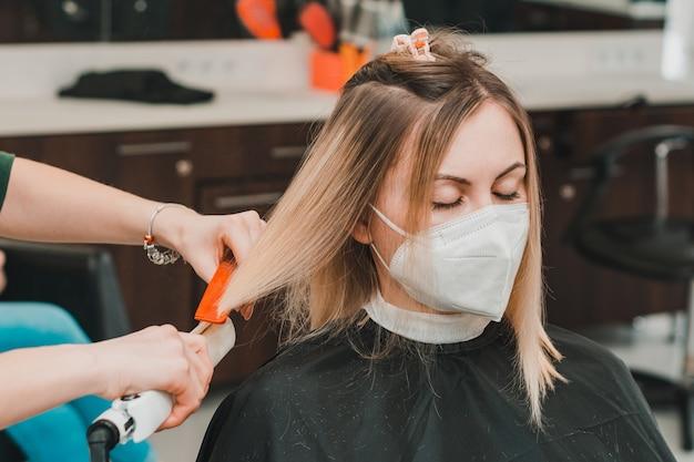 Haarverzorging, kapper knipt de afgeknipte haarpunten en maakt de lengte recht, het werk van kappers tijdens de wereldwijde coronaviruspandemie. nieuw