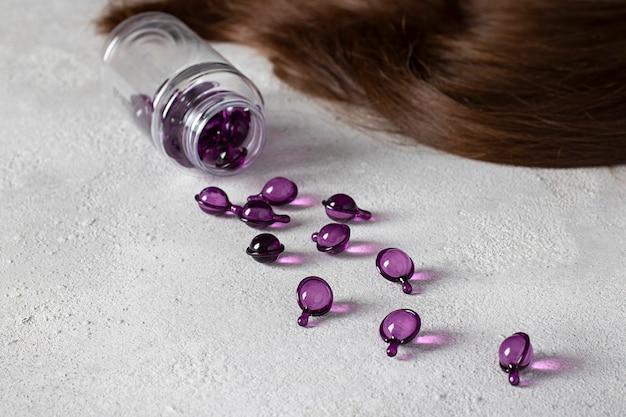 Haarvitaminecapsules op een grijze achtergrond: haarbehandelings- en verzorgingsproducten met olie voor beschadigd, gehighlight, gepermanent en gekleurd haar