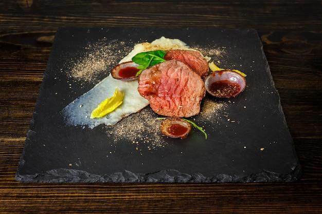 Haasbiefstuk met rode saus en aardappelpuree op schalieplaat
