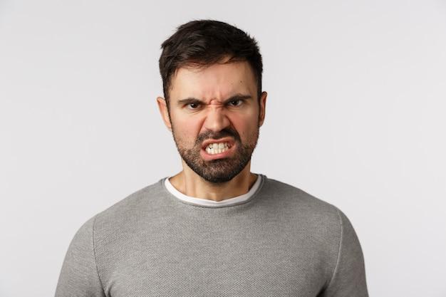Haat, emoties en agressie concept. haatdragende, woedende blanke bebaarde man in grijze trui, grijnzend fronsen kijken geschokt en boos, grijnzende gebalde vuisten, willen stomp vijand,