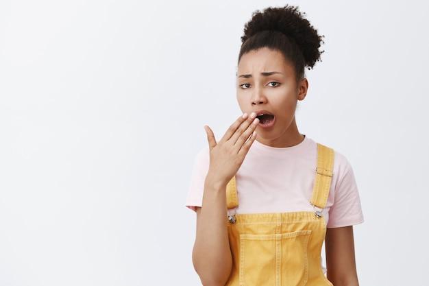 Haat saaie mensen. onverschillige vermoeide en verveelde arrogante afro-amerikaanse vrouw met krullend haar in gele overall, geeuwend en geopende mond bedekt met handpalm, onzorgvuldig en ongeïnteresseerd