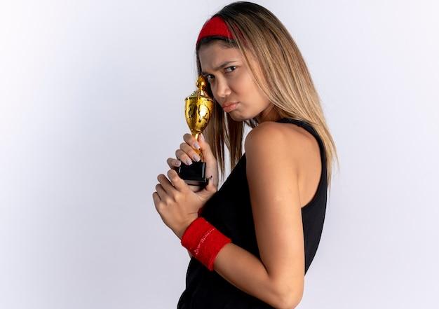 Haatdragend jong geschiktheidsmeisje in zwarte sportkleding en de rode trofee die van de hoofdbandholding zich over witte muur bevinden