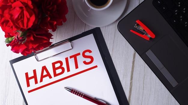 Habits is in het rood geschreven op een wit kladblok naast een laptop, koffie, rode rozen en een pen.
