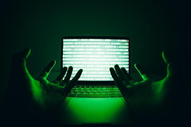 Hacker die de laptopcomputer gebruikt om virussen of malware te coderen voor het hacken van de internetserver