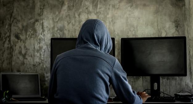 Hacker, hacker hackt netwerk, hacker op een donkere achtergrond. gevaarlijke hacker met kap breekt in op overheidsgegevensservers