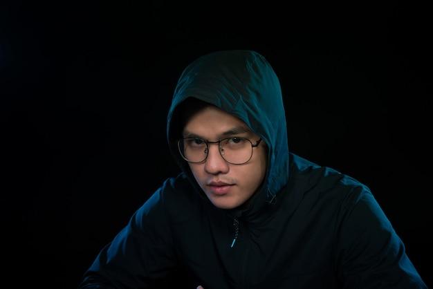 Hacker in een donkere hoody zit voor een notebook. aanval op computerprivacy