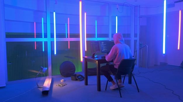 Hacker in witte hoodie doordringend netwerksysteem in neon kamer