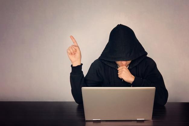 Hacker met een kap voor zijn computer toont vinger. donker gezicht. hooded .technology concept, hacker wijst vinger naar lege ruimte voor tekst.