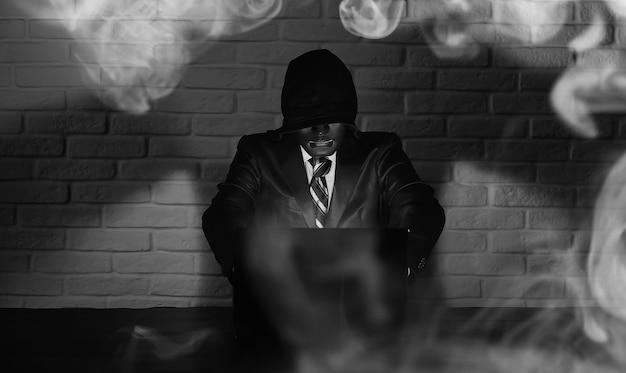 Hacker met zwart masker en kap aan de tafel voor de monitor