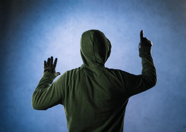 Hacker van achteren aan de muur