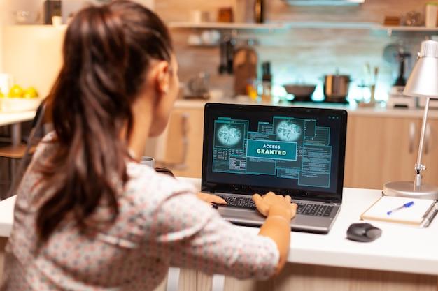 Hackervrouw lanceert 's nachts vanuit huis een cyberaanval op de firewall van de bank. programmeur die een gevaarlijke malware schrijft voor cyberaanvallen met behulp van een prestatielaptop tijdens middernacht.